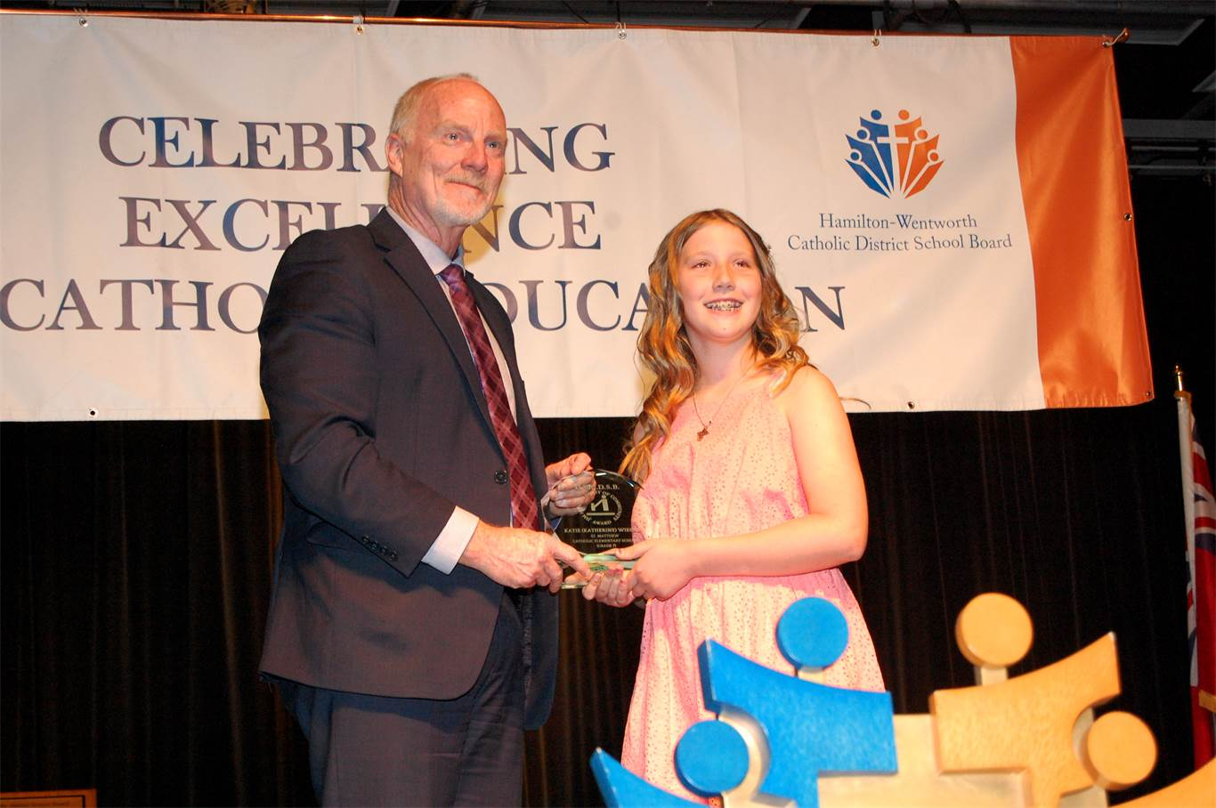 David Hansen presents Katherine Wiesner with the James Hansen Spirit of Community Award. The award, in recognition of former Superintendent Jim Hansen's legacy of 'Each Belongs,' is presented annually to one elementary and one secondary student who, by their presence and actions, serve as builders of community.